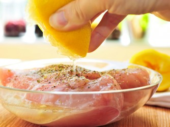 Hand marinating raw chicken breasts