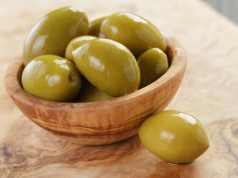 salted giant green olives in olive bowl on wooden table