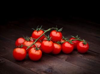 Ripe cherry tomatoes on dark wood background