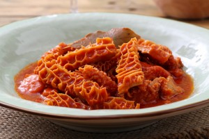 tradional tripe in tomato sauce in rustic ceramic plate on kitchen table background