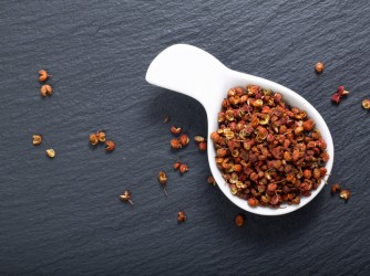 Chinese pepper, Sichuan pepper in white ceramic cup on black slate stone plate with copy space