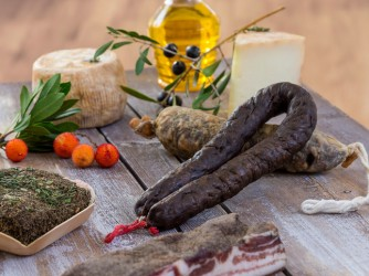 several variety of traditional Corsican charcuterie with an olive branch and black olives on wooden background