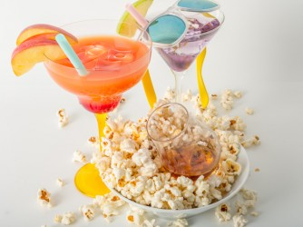 Two color drinks and whisky single malt, salty popcorn in a bowl and scattered aroun