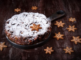 Traditional Christmas cake Panforte and gingerbread cookies in the shape of snowflakes on dark wooden table
