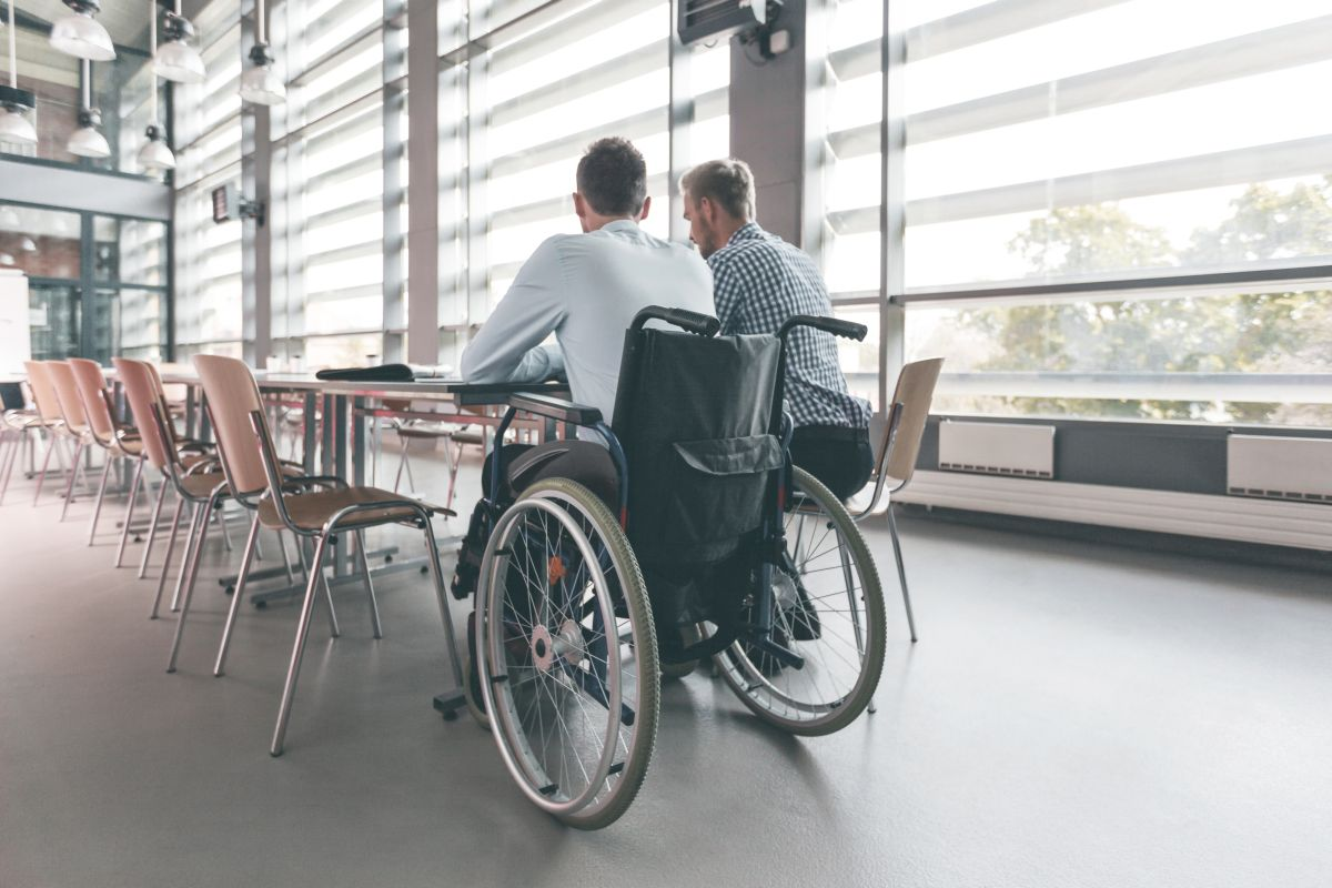 Disabled businessman working with his colleague in an office