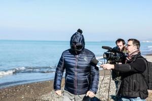 Bebbe Grillo con la maschera  fa footing in spiaggia