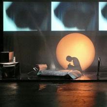 Un'ombra racconta accanto al letto di lamiera