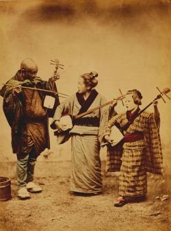 Felice Beato, Giappone, Suonatori ambulanti, 1868. Stampa all'albumina colorata a mano