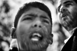 """Libia, aprile 2011. """"Sul cassone di un camion che trasporta la bara di un martire della rivolta anti-Gheddafi questo ragazzino di dieci o undici anni piange e grida. Il morto era un suo parente, ma quello non è solo il dolore di una perdita. Vedere un bambino che urla così la sua rabbia, non è una cosa normale»."""