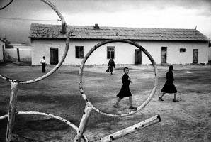 """Khodjely City, Uzbekistan, Mare di Aral, Ottobre 1997 Scuola Repubblicana di accoglienza per bambini affetti da gravi malformazioni. La fotografia rispetto alla pittura consente la cattura dell'istante , il suo congelamento visivo preso """"dal vero"""". La street photography, l'ideologia dell'istantanea o ancora meglio le regole etiche imposte dal giornalismo restituiscono attraverso il mezzo meccanico fotografico questa possibilità precipua. Poi, dietro l'obiettivo, è l'universo di valori e di cultura di chi sceglie l'inquadratura, la lente e l'istante a fare la differenza. Distintiva in molta fotografia italiana dal dopoguerra in poi è la visione prospettica, la composizione secondo le regole della simmetria , lo sforzo di sfruttare il mezzo meccanico al fine di congelare l'attimo. In questa mia fotografia riconosco questa tradizione, ma anche un invito a creare delle tensioni dinamiche """"di rottura"""" della tradizione."""