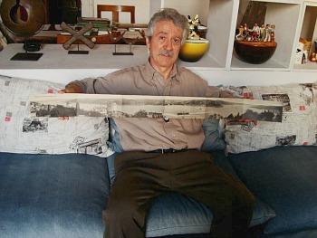 Enrico Sturani con la cartolina più lunga del mondo, una nonupla con la veduta dell'intero Bosforo in una botta sola. I cuscini su cui s'appoggia, ovviamente, sono illustrati a cartoline. Sullo sfondo, le ceramiche dei primi anni Trenta, opera del padre Mario Sturani