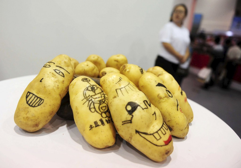 Potatoes painted with faces and cartoons are seen on display during the World Potato Congress on the outskirts of Beijing