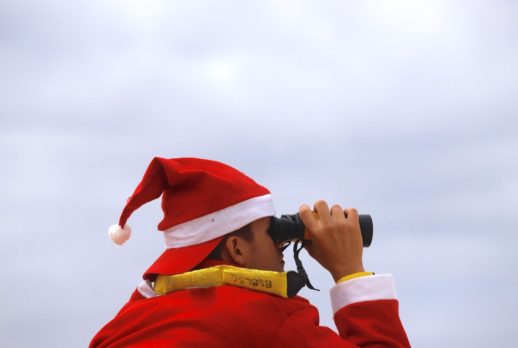 A surf lifesaver wearing a Christmas hat uses binoculours to watch swimmers on Christmas Day at Sydney's Bondi Beach
