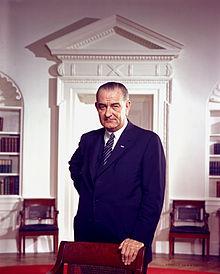 220px-Lyndon_B._Johnson,_photo_portrait,_leaning_on_chair,_color