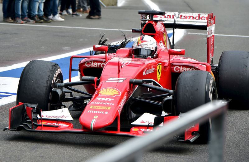 Ferrari Formula One driver Vettel of Germany drives in the pit lane after a tyre failure during the Belgian F1 Grand Prix in Spa-Francorchamps