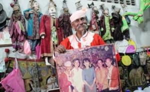 Par Par Lay tra gli abiti di scena, regge un ritratto con Aung San Suu Kyi. Foto Irrawaddy