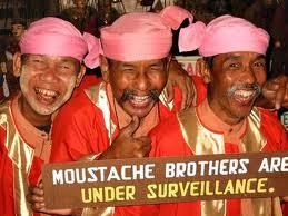 """I Moustache brothers con un cartello che esibivano negli show nonostante fossero - come è scritto in inglese - """"sotto sorveglianza"""""""
