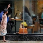 Piccola mendicante fuori da un caffè di Mumbai