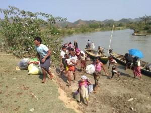 Profughi scappano in barca dai combattimenti in corso a un'ora da Sittwe.