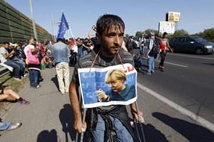 Migranti: in cammino con ritratti di Merkel e bandiere Ue