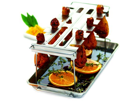 Per cucinare cosce e alette di pollo in modo uniforme, il supporto dei Signori del Barbecue. ll vassoio raccoglie i succhi della carne in cottura <br>e può contenere erbe aromatiche e altri ingredienti. In acciaio inox, 34 euro
