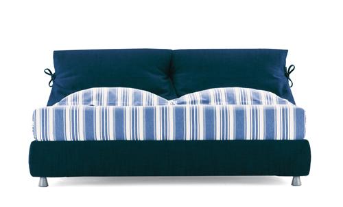 Nathalie di Flou è il primo letto tessile di Vico Magistretti. L'imbottitura della testata prosegue anche nella parte posteriore ed è fissata con un fiocchetto. Il letto è completamente sfoderabile