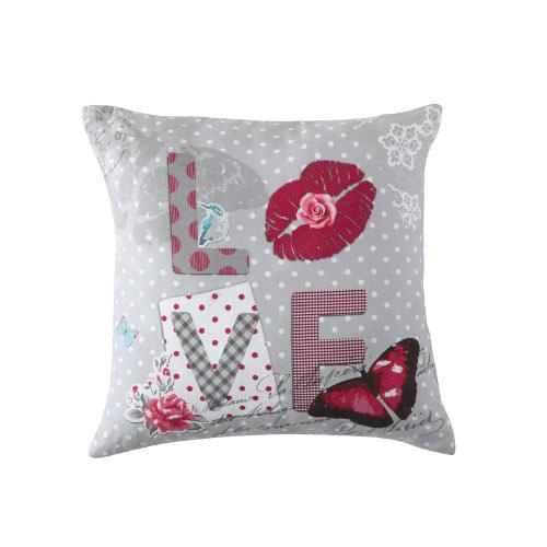"""Nel cuscino di Maisons du Monde la parola chiave """"love"""" è accompagnata da una fantasia che si distingue per l'utilizzo di pizzi, pois e quadrati (11,99 euro)"""