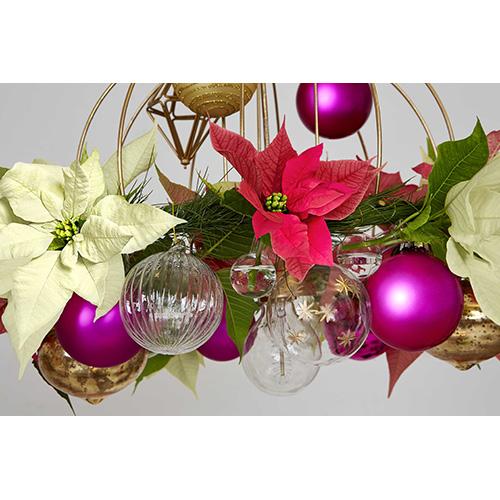 Un semplice paralume decorato può prendere il posto della classica lampada da soffitto durante il periodo natalizio se arricchito con dei fiori di Poinsettia recisi, dei rametti di abete e delle decorazioni. Ricordate di utilizzare una lampada Led che non si surriscaldi e quindi non possa danneggiare il fogliame