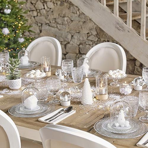 Una tavola non richiede necessariamente una tovaglia. Come quella di Maisons du Monde che punta su uno stile nordico evocando i paesaggi innevati. Preferisce le trasparenze del vetro alla ceramica che accosta al legno naturale del tavolo e alle decorazioni bianche