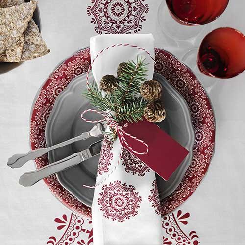La proposta di Ikea è tradizionale e gioca con i due colori tipici del Natale, il bianco e il rosso. Inoltre, la tavola è impreziosita da elementi naturali: le pigne e i rami sempreverdi di stagione sono a corredo del tovagliolo che funge da segnaposto