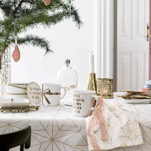 H&M Home  apparecchia la tavola con stoviglie che si caratterizzano per dettagli color oro. Anche la tovaglia si veste a festa riprendendo il tema delle stelle