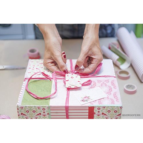 Dopo aver inserito il regalo puoi chiudere la scatola con un nastro per pacchi (oppure un filo di lana, spago, raso, rafia, ect) ma prima ritaglia con le forbici un'etichetta rettangolare da un cartoncino colorato, perforala sul lato più corto e lascia passare il nastro di chiusura all'interno del foro. Fai un bel nodo e il gioco è fatto!