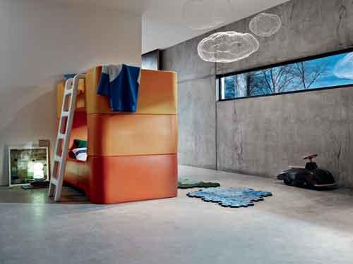 Magis, Bunky di Marc Newson e Puzzle Carpet di Satyendra Pakhalé. Letto a castello in polietilene stampato con stampaggio rotazionale comprensivo di materasso, coprimaterasso, cuscino, federa e set lenzuola. Disponibile in arancione e in blu. A destra, il tappeto in polietilene espanso morbito accoppiato di tessuto poliestere, disponibile in blu, beige e verde. Courtesy of Magis, foto di Max Rommel