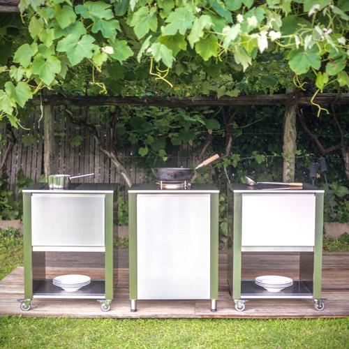 Jokodomus, collezione Cun da giardino. Per cucinare in giardino ci sono questi 3 elementi. Da sinistra: carrello da cucina in acciaio inox con piano di cottura a induzione 2 zone, con un cassetto e un ripiano inferiore. Il secondo elemento invece ha un wok a gas 12 kW, con un vano porta bombola. Il terzo elemento, infine, vanta un piano cottura Teppanyaki 2 zone