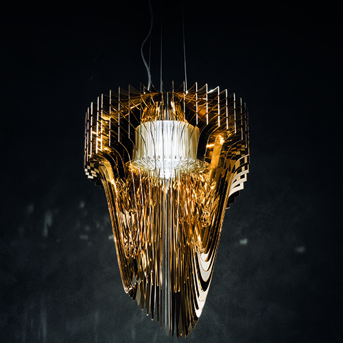 È uno degli ultimi lavori di Zaha Hadid e ha tutte le carte in regola per diventare un nuovo classico. La lampada a sospensione Aria di Slamp, qui proposta nella versione gold, è realizzata in policarbonato trasparente metallizzato con polvere d'oro brillante (2.300 euro)
