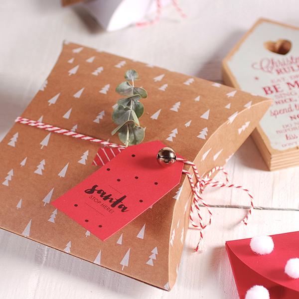 Scatola regalo natalizia con abeti. Arricchita da etichetta natalizia, baker's twine, campanellini e washi tape rosso. Dove acquistarla? Su www.selfpackaging.it. Prezzo scatola 1,52 euro