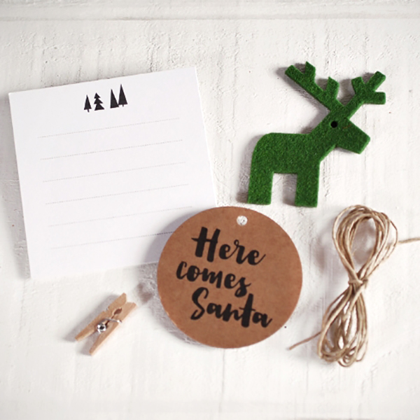Kit accessori per regali di Natale disponibile su Self packaging. Include: etichetta rotonda Here comes Santa, cervo in feltro verde, cordoncino in canapa, biglietto per scrivere un messaggio e mini molletta. Prezzo 2,30 euro