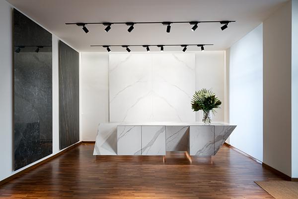 All'ingresso dello showroom  alcuni esempi di applicazioni in arredamento delle lastre ceramiche, come tavoli e cucine sulle quali spiccano tonalità delicate e le venature naturali del marmo