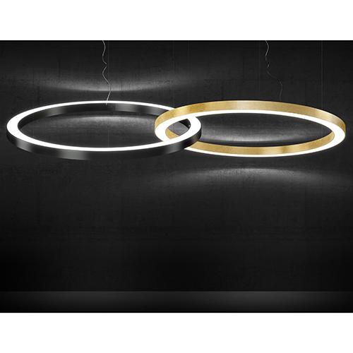 Come una promessa d'amore, Silver Ring è la luce progettata da Enzo Panzeri per l'omonima azienda di famiglia. Due anelli in alluminio che si intrecciano per illuminare e personalizzare gli interni. Si possono creare varie combinazioni con altri cerchi di diversa dimensione, sia della stessa collezione sia della Golden Ring. Nelle versioni a parete e sospensione