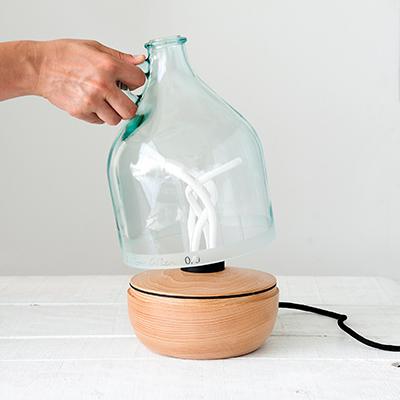"""Altra opera di Lucia Bruni, firmata studio <a href=""""http://www.lucirmas.com/"""">Lucirmás</a>, è <em>Dama Lamp</em>: un punto luce da tavolo che nasce dal riuso di una caraffa da 5 litri posizionata su una base in legno (anche questa lavorata a mano da alcuni artigiani). Fotografia di VictorMax©Photo"""