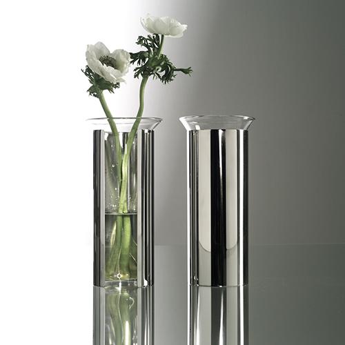 Il vaso da fiori Camicia, firmato da Enzo Mari nel 1961, è un oggetto semplice ed elegante, composto da un cilindro in metallo, senza fondo, che sostiene un contenitore di vetro trasparente facilmente sfilabile. Il foro e il taglio verticale a tutta altezza, praticati nel cilindro, permettono di vedere anche la parte del fiore che sta nell'acqua