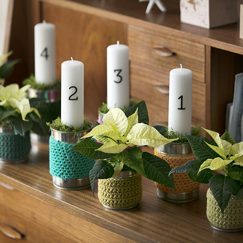 Per creare questa corona dell'Avvento sono necessari quattro lattine grandi e quattro piccole con coperture in crochet, quattro Stelle di Natale mini, quattro candele natalizie numerate, spugna floreale, muschio
