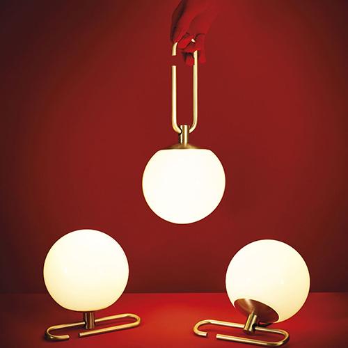 """<em>Nh1217</em> di <a href=""""http://www.artemide.it/"""">Artemide</a> si caratterizza per una una sfera in vetro soffiato bianco che scorre lungo un anello in ottone spazzolato. La struttura permette quindi di orientare liberamente il diffusore e funge sia da base d'appoggio che da gancio per appenderla (190 euro)"""