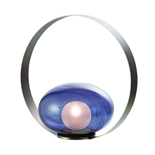 """Quando la materia diventa struttura e decoro: è <em>Voilà</em> la scenografica lampada da appoggio di <a href=""""https://www.roche-bobois.com/it-IT"""">Roche Bobois</a>. È realizzata in vetro di Murano soffiato, l'anello è in acciaio (770 euro)"""