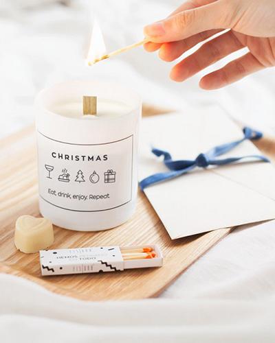 """Dona una luce calda ed è subito festa grazie alla candela con decori natalizi di <a href=""""https://www.fisura.com/"""">Fisura</a>. Disponibile nelle tonalità del bianco e del rosso. Prezzo 11 euro"""