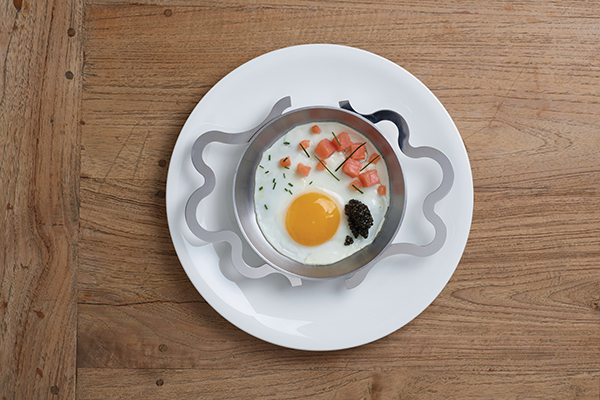 """Finalmente in cucina. Il maestro del design Alessandro Mendini con <a href=""""http://www.alessi.com"""">Alessi</a>, e la collaborazione di Alex Mocika e Alberto Gozzi, ha disegnato il tegamino perfetto. <em>Tegamino</em> permette di preparare, servire e consumare un alimento semplice come l'uovo"""