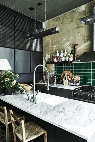 Un ex garage abbandonato di Amsterdam è stato trasformato in una casa piena di carattere. La cucina  si caratterizza per i piani di lavoro in marmo, le attrezzature in acciaio inox, le luci al neon e le tubazioni a vista