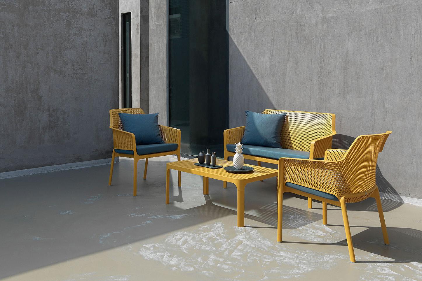 """Il sistema di arredo <em>Net</em> di <a href=""""http://www.nardioutdoor.com"""">Nardi</a> si distingue per la decorazione a fori quadrati distribuita uniformemente su tutta la superficie sia delle sedute che del tavolino. Disponibile in bianco, antracite, senape, corallo, salice e tortora, la serie può essere personalizzata con cuscini in tinta oppure a contrasto"""