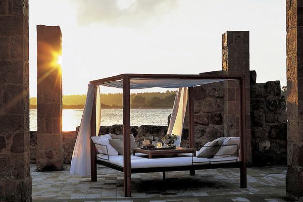 Il gazebo da giardino <em>Oasis</em> di Roda unisce il relax con la convivialità. La struttura ombreggiante può essere personalizzata aggiungendo un piano di appoggio in teak  e schienali per rendere ancora più comoda la seduta