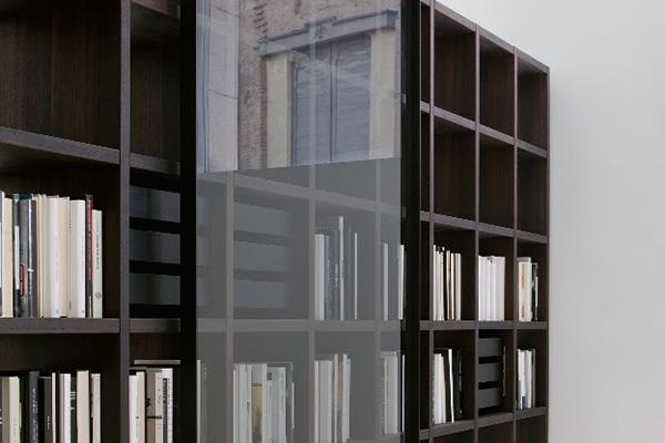 """Libreria, contenitore, area studio o anche elemento per suddividere ambienti: è <em>System</em> di <a href=""""http://www.porro.com"""">Porro</a> qui con anta scorrevole in cristallo trasparente"""